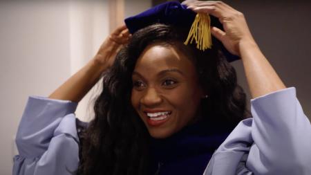 Kizzmekia Corbett puts a gradution cap on.