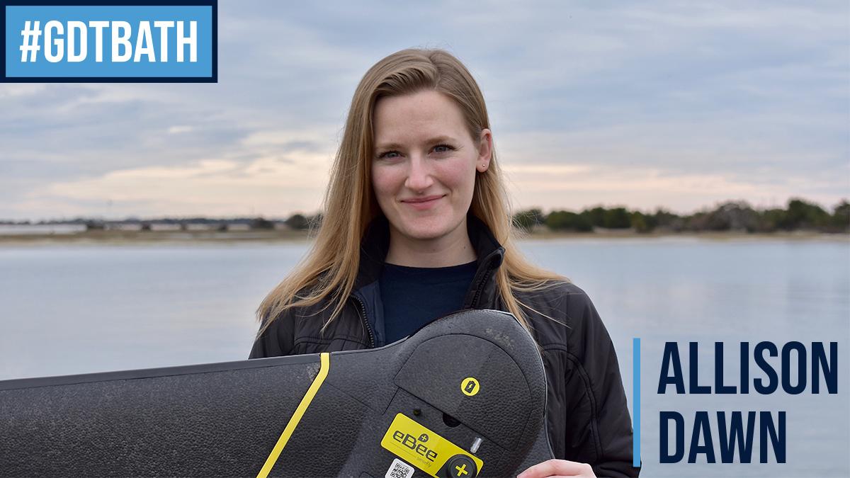 Allison Dawn holds a drone near the shore.