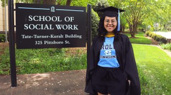 Daniela Ceron in her cap and gown by the School of Social Work.
