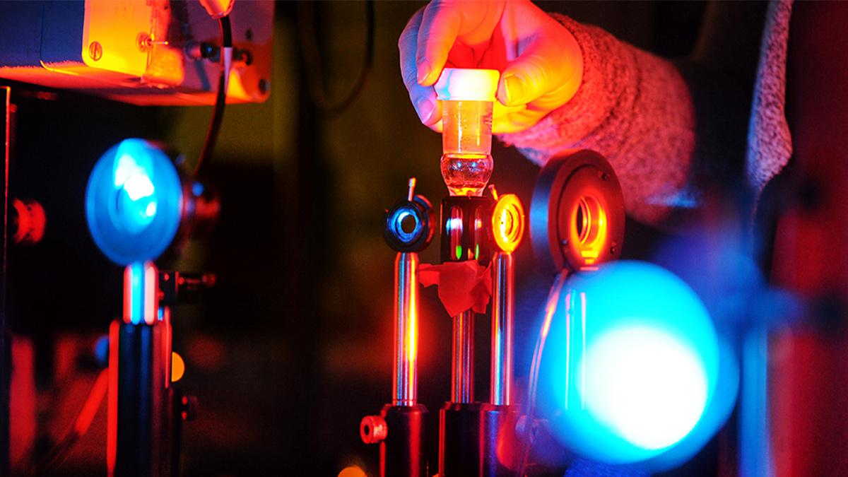 A person adjusts a laser tool.