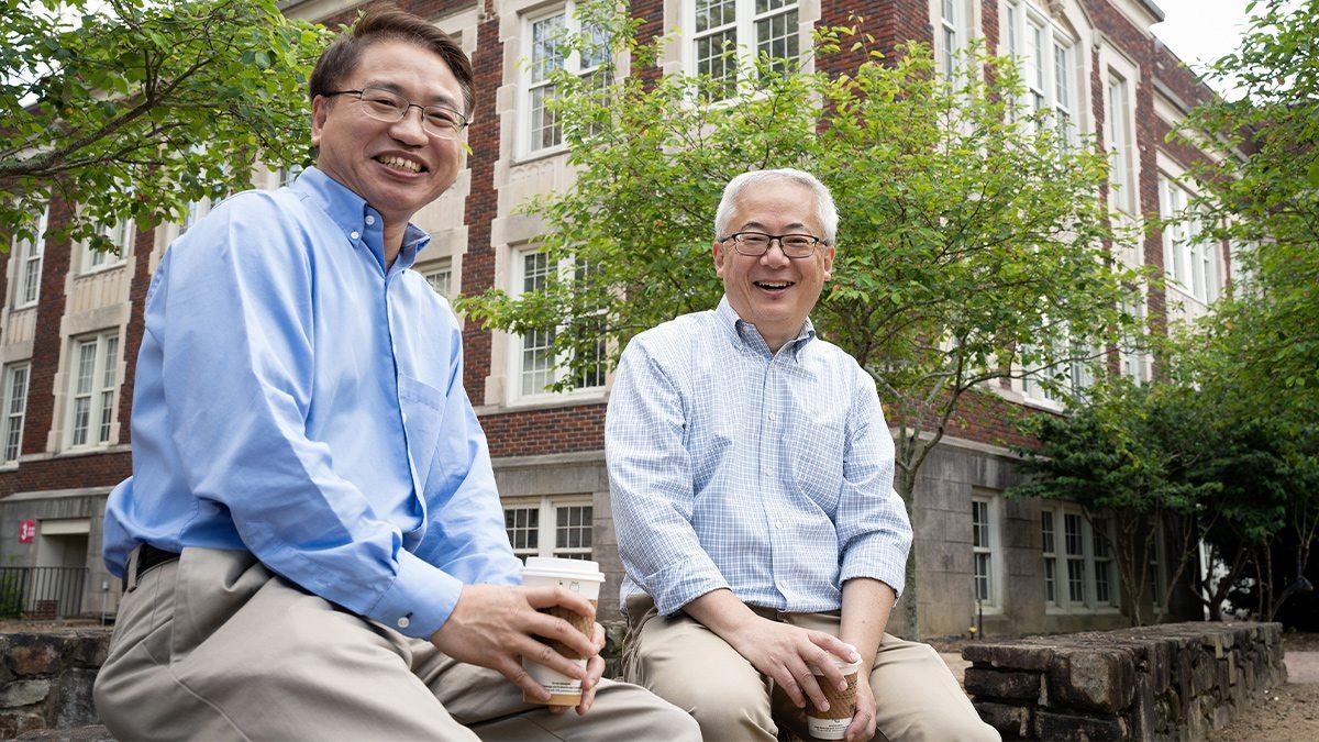 Jianping Lu and Otto Zhou sitting on a stone wall.