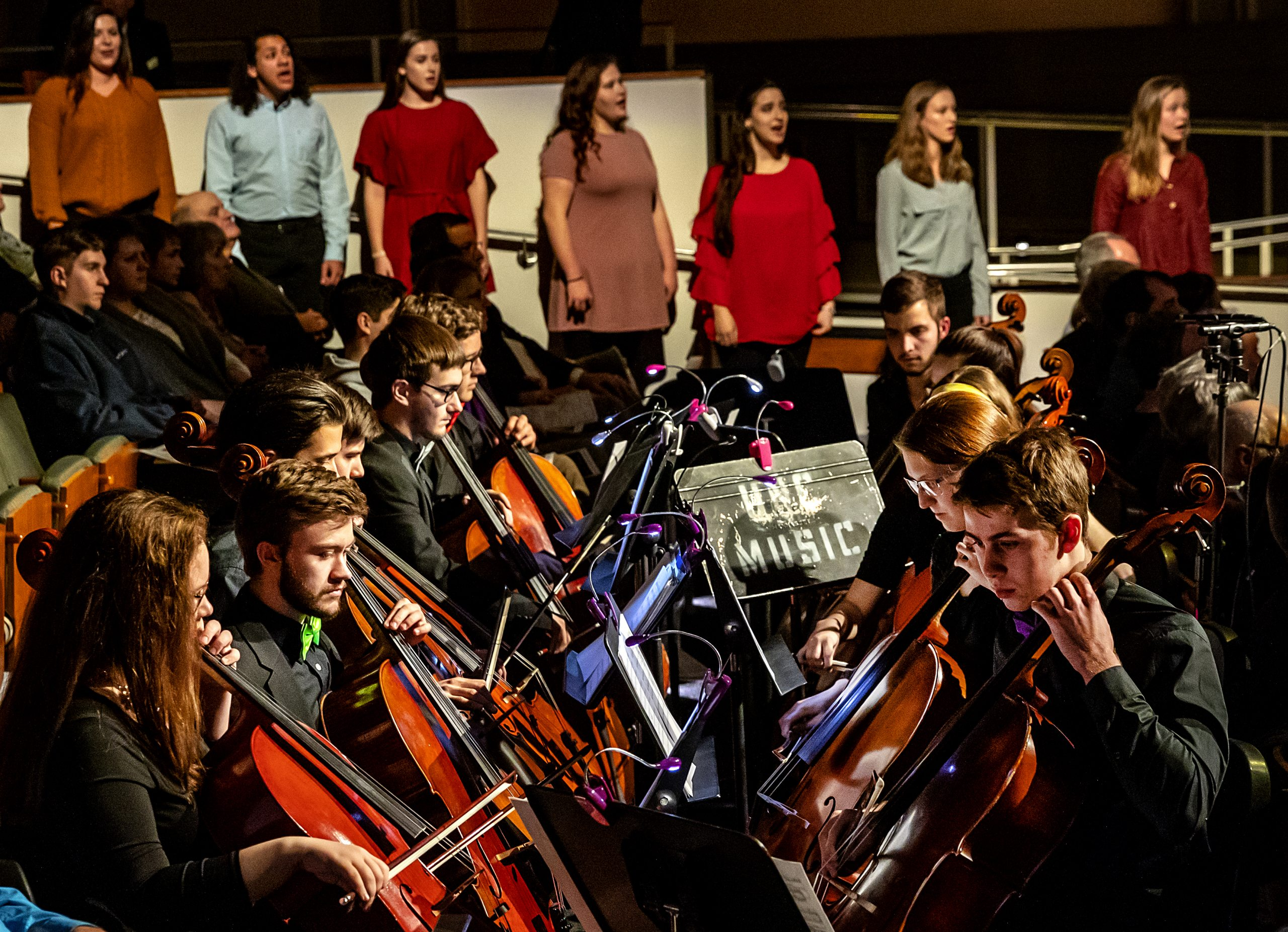 Musicians from the Department of music play their cellos during the Spectrum Concert. In the background, a choir stands side-by-side, singing.