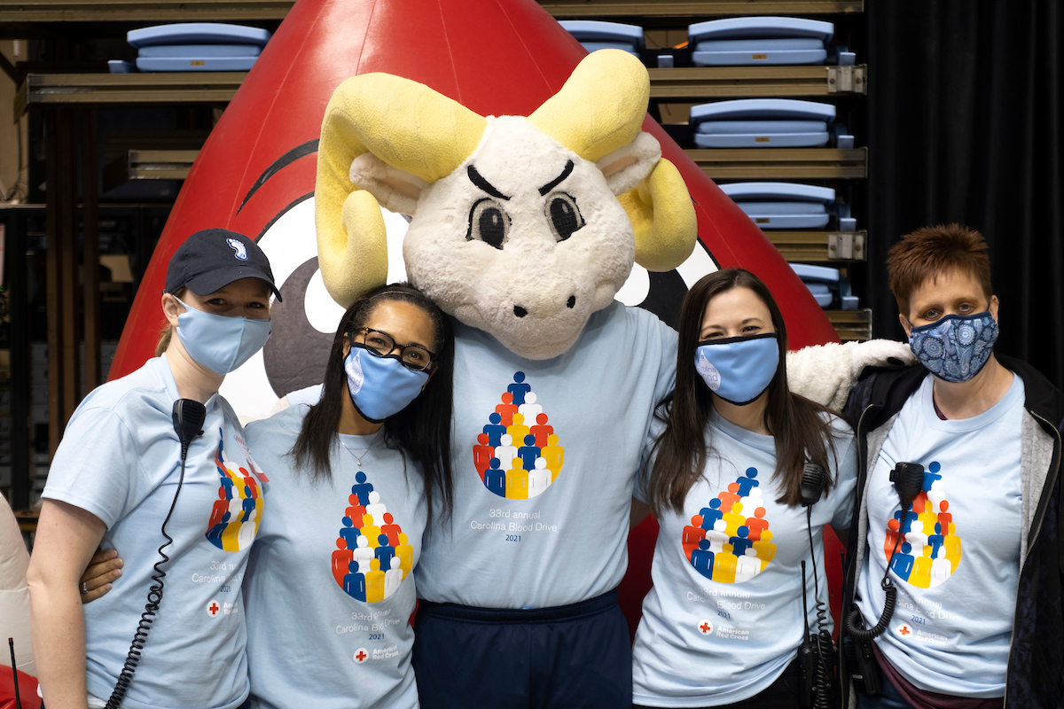 A group of blood drive organizers pose for a photo with Rameses.