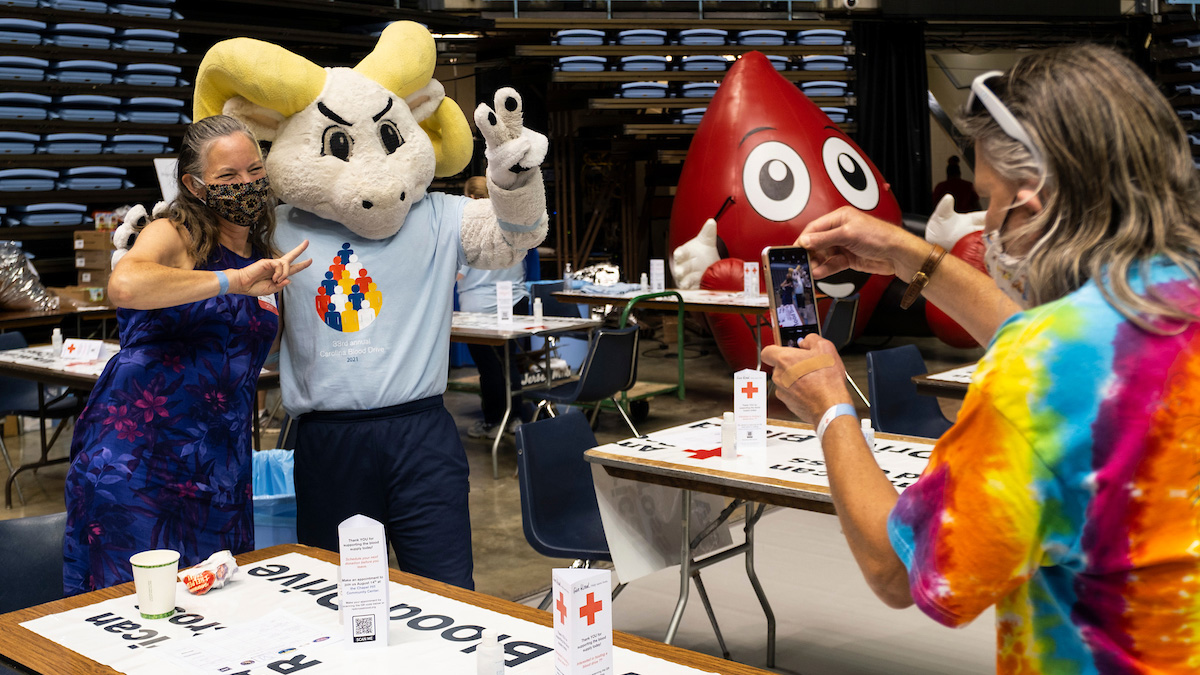 Rameses takes a photo with a blood drive donor.