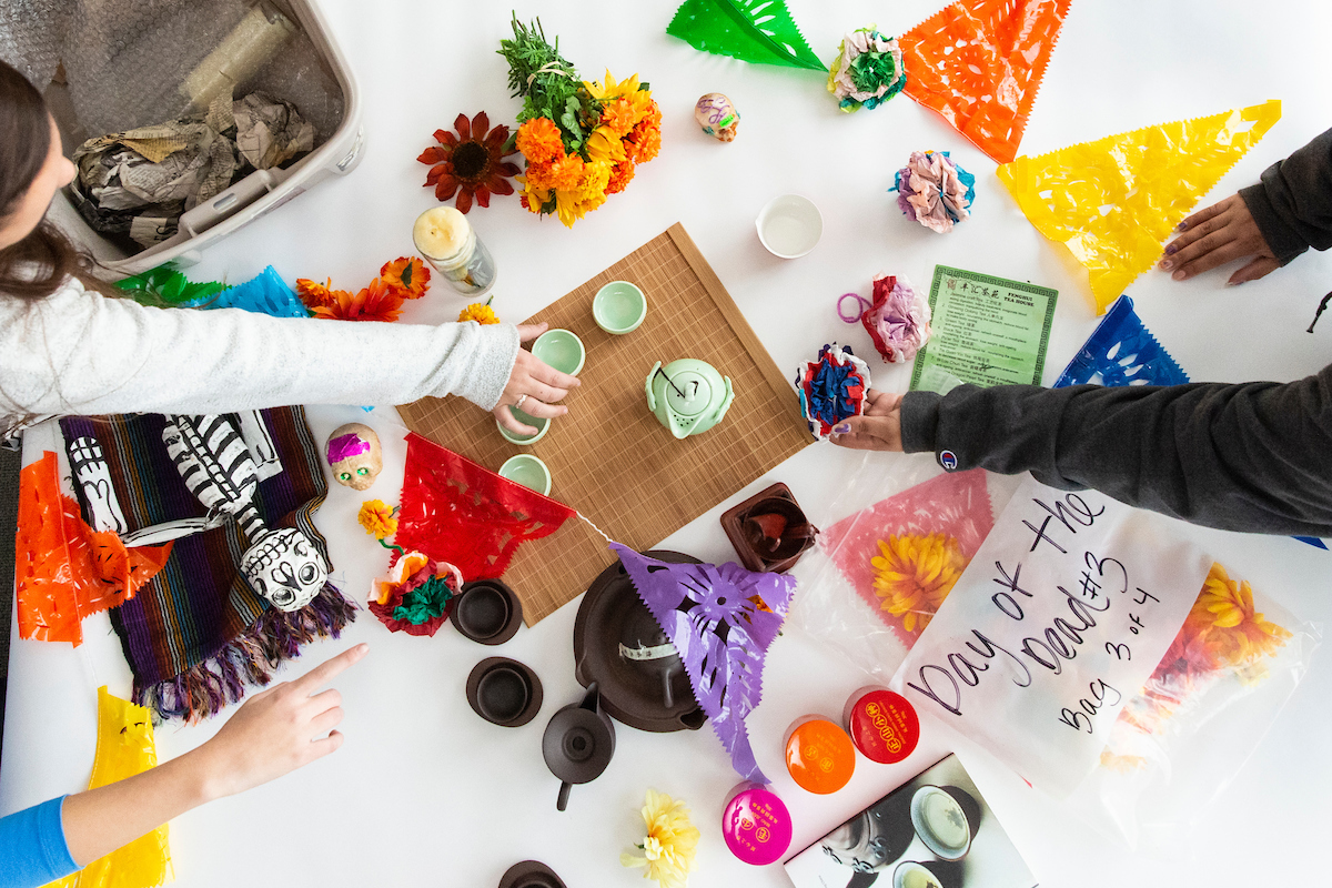 Students assemble culture kits on a table.