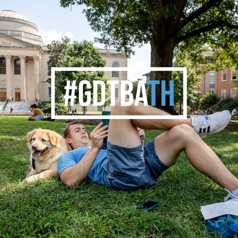 A male student sitting on Polk Place with his dog.