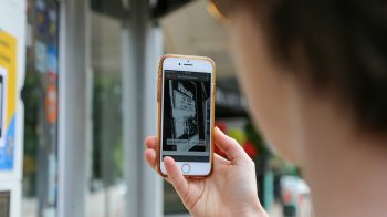 A person uses their phone to access the 'ARt Walk on Franklin' website.