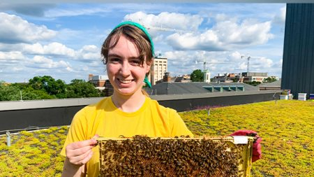 Addie Wilson holding a board with bees on it.