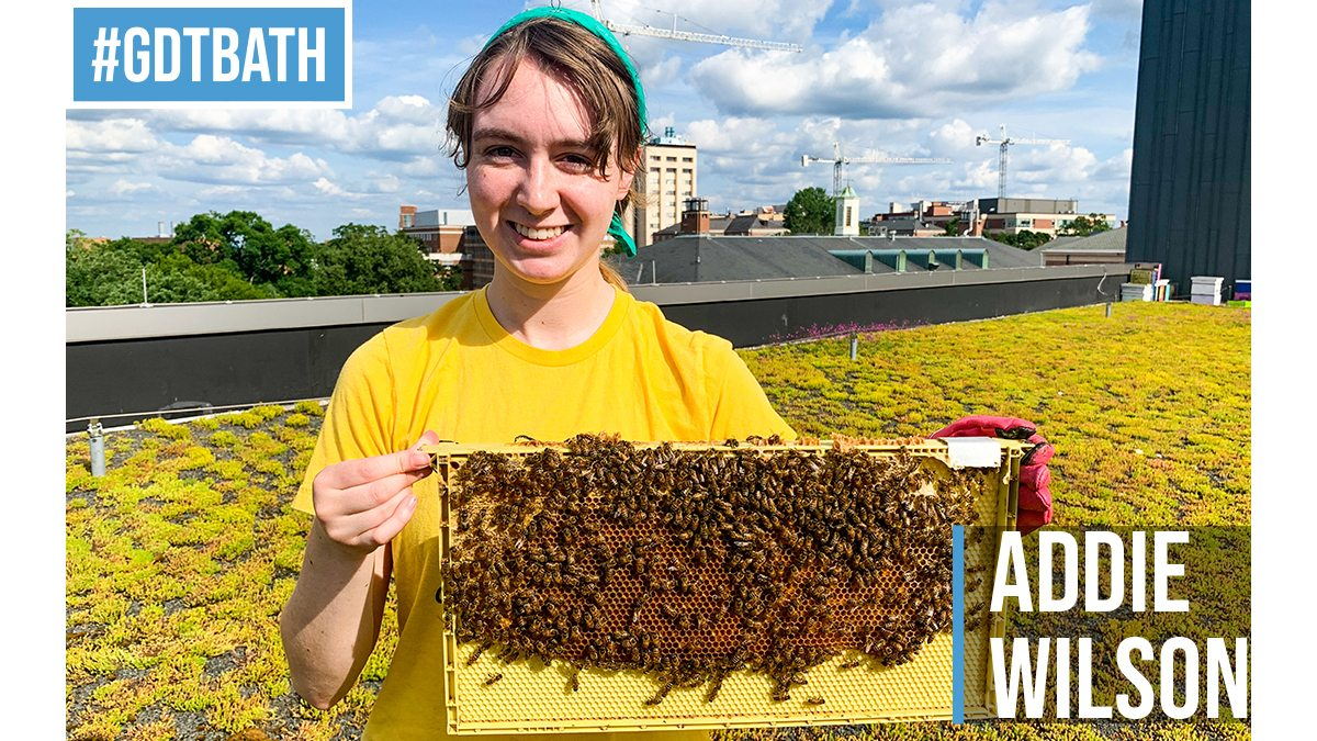 Photo of Addie Wilson on the roof of the Fedex Center holding a hive of bees.