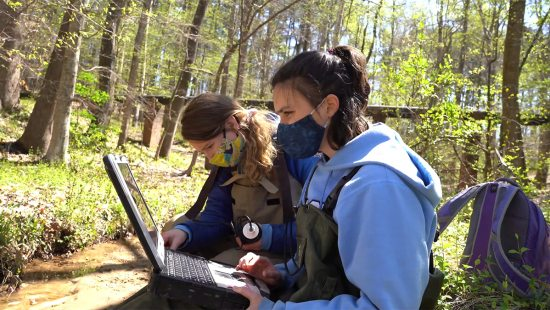 Two students working in a creek.