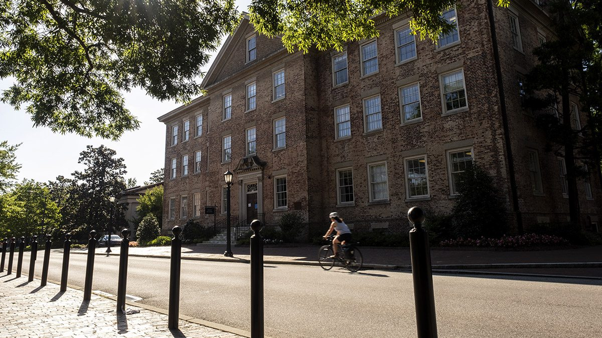 A person on a bike rides past South Building.