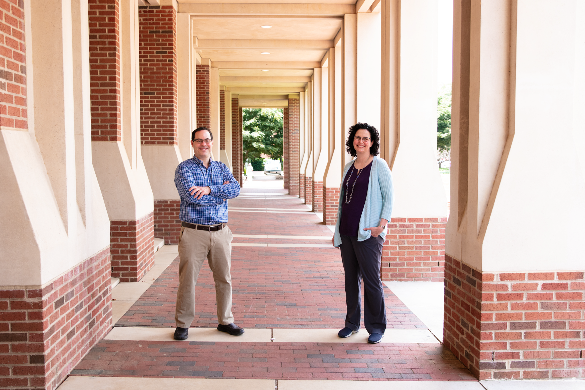 Brian Strahl and Samantha Pattenden stand outside by an academic building.