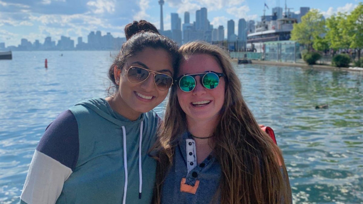 Jaya Mishra and Megan Lienau pose for a photo by the water.