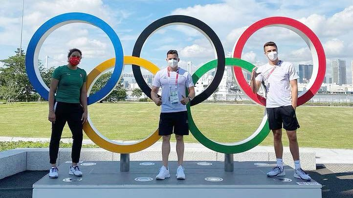 Three men standing near the Olympic rings.