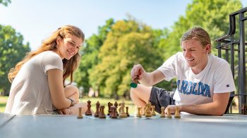 Victoria Sagasta Pereira and Peter Close play chess outside.