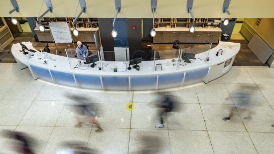 Students walk past the desk of Davis Library.