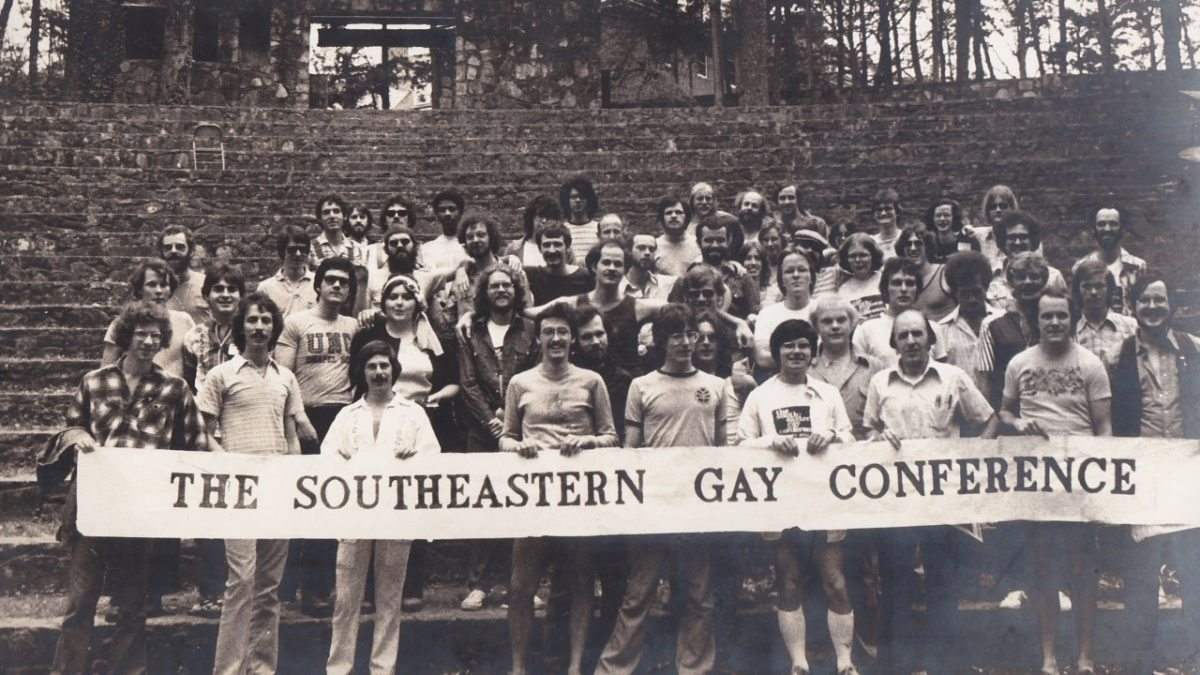 A group of students hold a banner that says