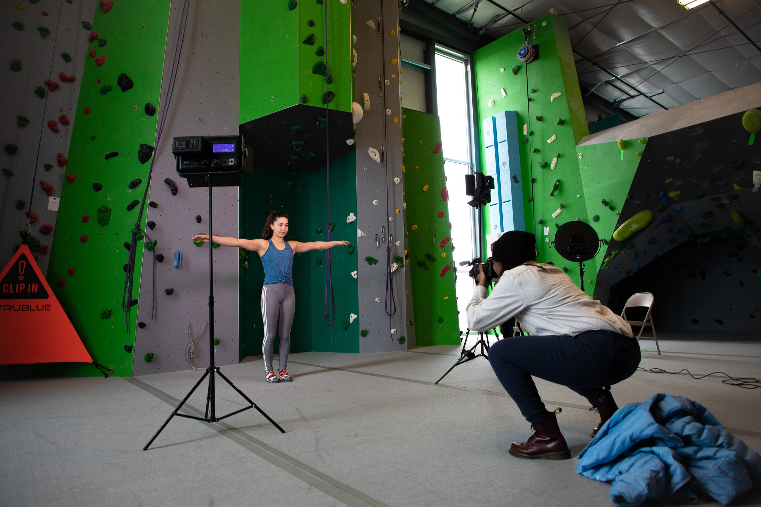 A Carolina student takes a photo of a climber in front of a rock wall.