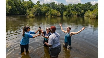 Four women standing in a lake collecting water samples.
