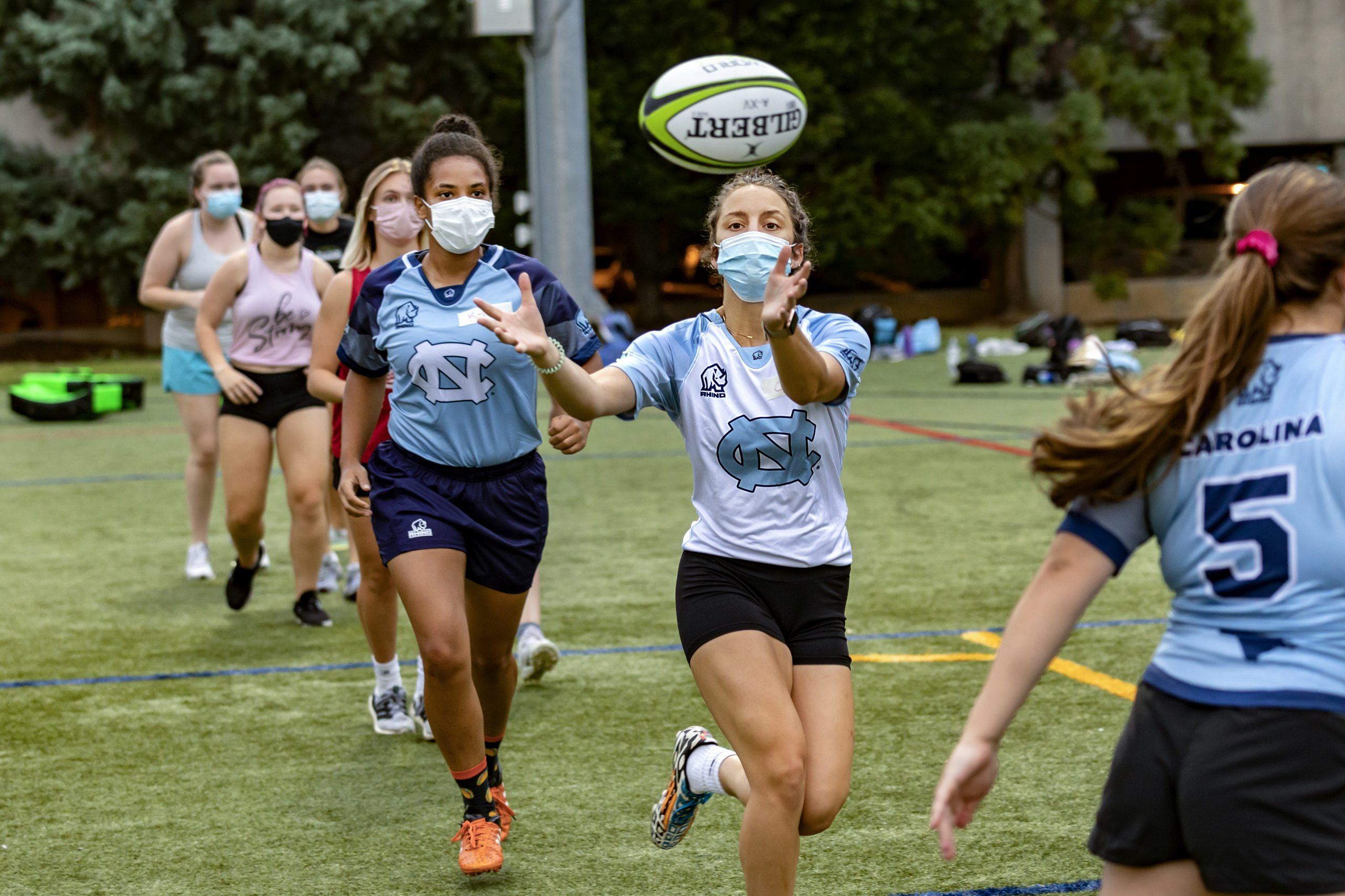 Students pass a ball at a rugby practice.