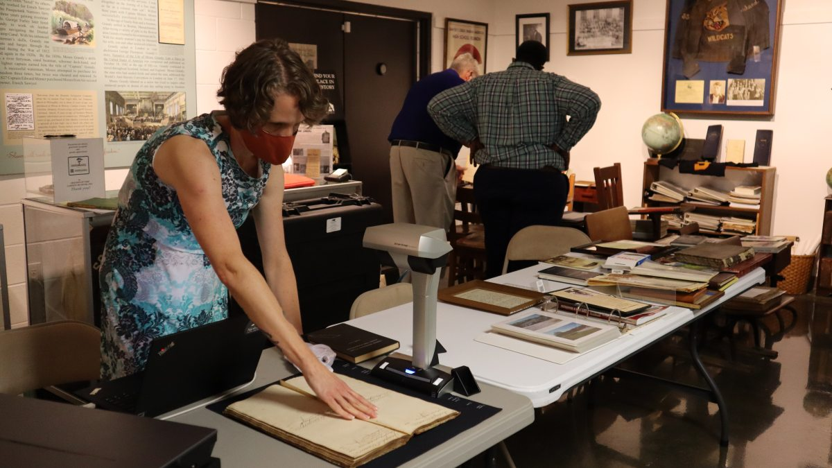 A woman uses a large scanner to scan a book.