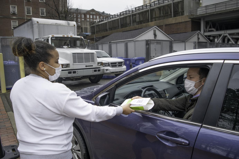 A person hands food to a person through a car door.