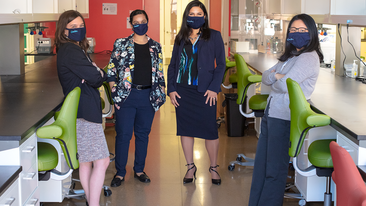 Four women standing in a research lab