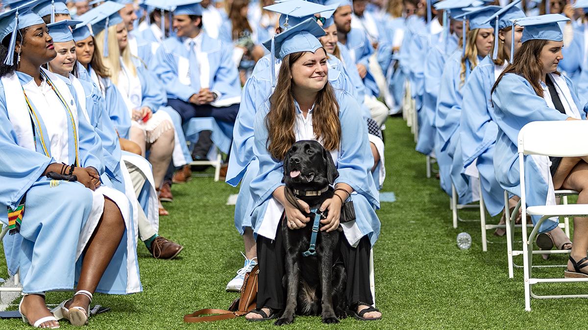 A graduate hugs their dog.