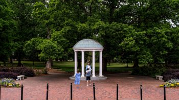 A student poses for photos by the Old Well.