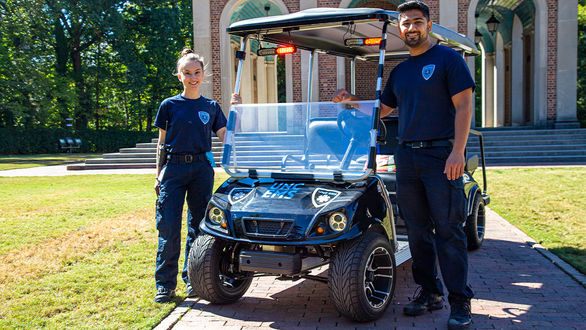 Sara Torzone and Ishan Khosla standing next to a golf cart.