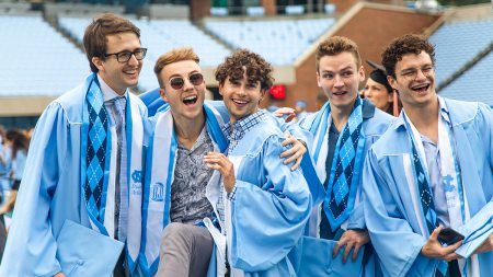 A group of men in graduation gowns celebrating.