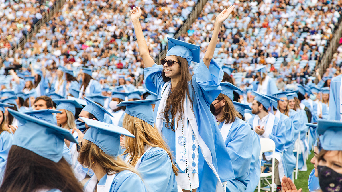 A women in cap and gown celebrates.