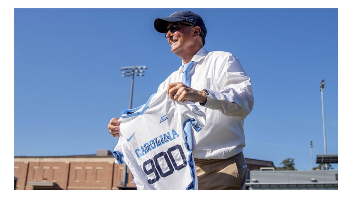 Anson Dorrance holds a Carolina women's soccer jersey with the number 900.