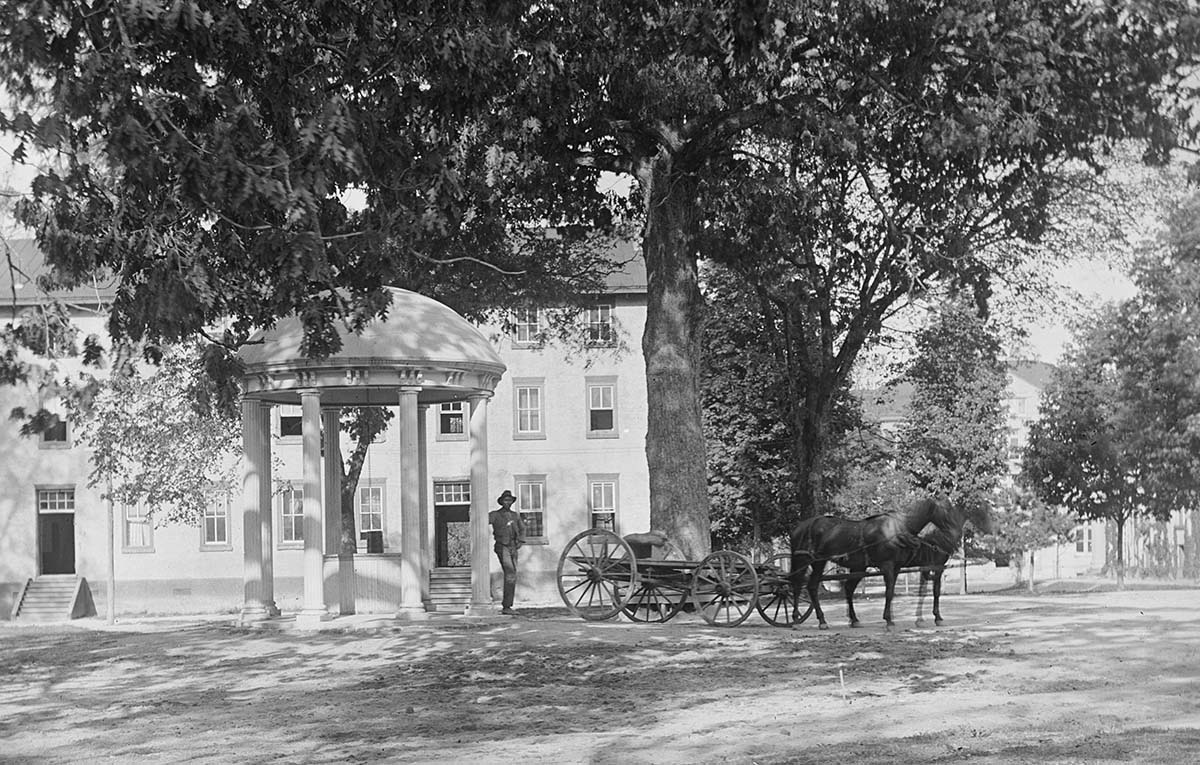 A black and white photo of a man at the Old Well.